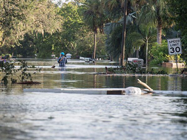 艾玛(Irma)飓风袭击佛罗里达州之后,9月11日人们在佛罗里达州那不勒斯的博尼塔温泉(Bonita Springs)的一个淹水的街区穿行。 (NICHOLAS KAMM/AFP/Getty Images)