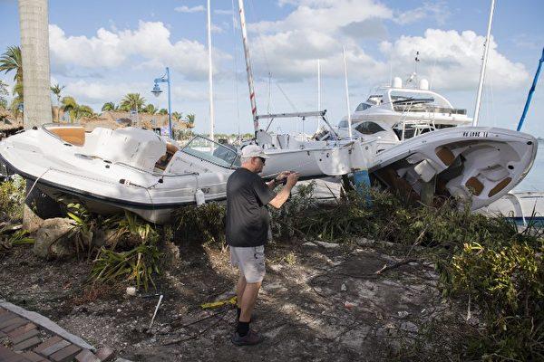 一名男子在9月11日在佛羅里達州邁阿密的一個碼頭拍攝艾瑪颶風損害的船隻。(AFP PHOTO / SAUL LOEB)