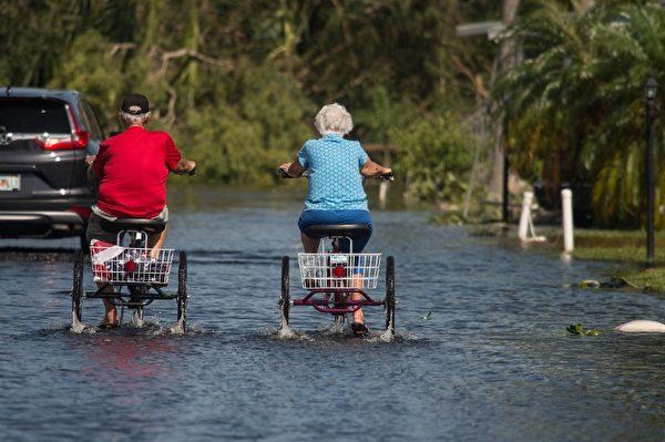 兩名老年婦女在佛羅里達州那不勒斯淹水街道上騎三輪車。(AFP PHOTO / NICHOLAS KAMM)