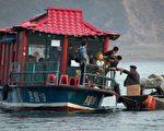 朝鮮男子(右)在鴨綠江沿岸向中國遊客出售朝鮮產品。( JOHANNES EISELE/AFP/Getty Images)