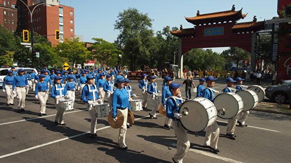 9月23日,来自加拿大魁北克省及安大略省几个城市的的部分法轮功学员在蒙特利尔举行了讲真相反迫害大游行。法轮大法天国乐团打头阵,图为天国乐团经过唐人街牌坊。(Nathalie Dieul / 大纪元)