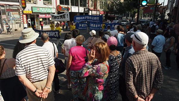 9月23日,来自加拿大魁北克省及安大略省几个城市的的部分法轮功学员在蒙特利尔举行了讲真相反迫害大游行。图为民众驻足观看游行队伍中法轮功真相横幅。(Nathalie Dieul / 大纪元)