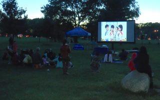 法拉盛民众扶老携幼来到皇后区植物园对面的大草坪上,观赏露天电影。 (韩瑞/大纪元)