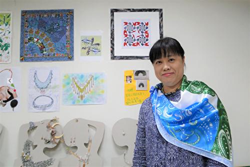 杨馨怡局长试戴学员徐谦的数位印花方巾作品。(谢平平/大纪元)