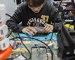 手机维修小店修理各个品牌手机的故障,满足了许多普通消费者的需要。图为香港一家二手手机店里,店员在维修手机。(ISAAC LAWRENCE/AFP/Getty Images)