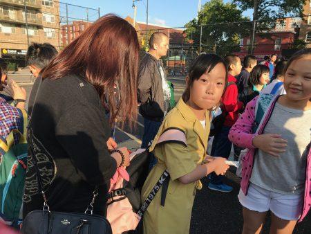 开学第一天,华人家长为孩子整理书包。
