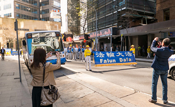 9月8日,法輪功學員的遊行隊伍經過悉尼市中心時,一些華人舉起手機拍照。(冼楚棋/大紀元)