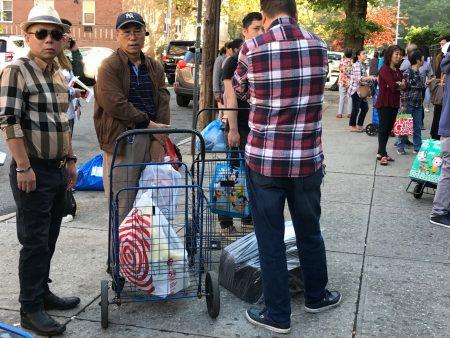 开学第一天,孩子的文具太多,家长拉着购物推车为孩子送文具回校。