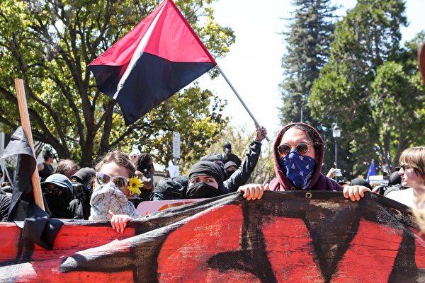 """""""反法""""(Antifa)抗议者和右翼反马克思抗议者8月27日在伯克利的马丁路德金公园对峙。(AMY OSBORNE/AFP/Getty Images)"""