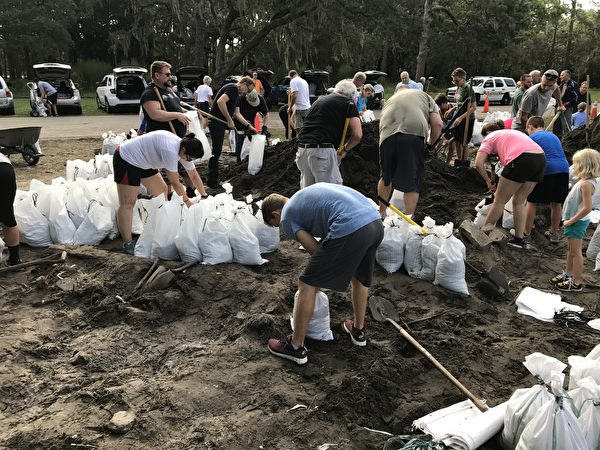 佛羅里達坦帕當地居民在整理已經裝好的沙袋。(周子定/大紀元)