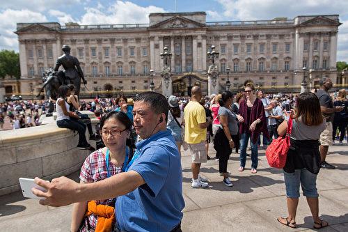 今年涌向欧洲的中国游客大增,图为中国游客在英国白金汉宫门前留影。(Rob Stothard/Getty Images)