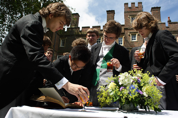 WINDSOR, UNITED KINGDOM - MAY 2008: Senior pupils sign the leavers book during a reception hosted by the headmaster of Eton College, Tony Little, in his garden for the school leavers before their departure at the end of the Summer term, at the iconic private school near Windsor, England. Eton College was founded in 1440 by King Henry VI. The College originally had 70 King's Scholars or 'Collegers' who lived in the College and were educated free, and a small number of 'Oppidans' who lived in the town of Eton and paid for their education. Eton has a very long list of distinguished former pupils, including eighteen former British Prime Ministers. (Photo by Christopher Furlong/Getty Images)