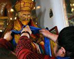 在这张未标明日期的照片中,一名信众正在装饰西伯利亚著名佛教领袖、寒波寺住持喇嘛伊谛吉洛夫(Dasha-Dorjo Itigelov)的肉身。伊谛吉洛夫1927年在布列亚特共和国首府乌兰乌德的一座寺庙去世,享年75岁。其肉身至今没有任何朽烂迹象。(HO/AFP/Getty Images)