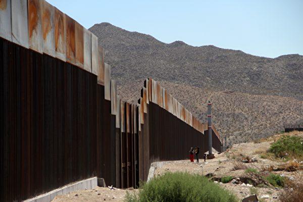 美墨边境墙的样板建设有可能在10月底前完成。图为2017年5月23日在墨西哥华瑞兹城与美国边境墙的一墨西哥家庭。(HERIKA MARTINEZ/AFP/Getty Images)