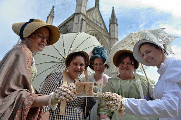 WINCHESTER, UNITED KINGDOM - JULY 18: People in period costume pose with one of the Bank of England's new ten pound notes, featuring British author Jane Austen, during its unveiling at Winchester Cathedral on July 18, 2017 in Winchester, England. Two hundred years after Jane Austen's death, Britain is celebrating one of its best-loved authors, who combined romance with biting social commentary that still speaks to fans around the world. Austen is buried in the cathedral in Winchester, where she died. (Photo by Chris J Ratcliffe-Pool/Getty Images)