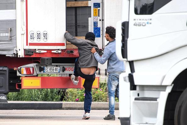 今年7月28日,企圖偷渡者在光天化日下偷偷進入開往英國的貨車。( DENIS CHARLET/AFP/Getty Images)
