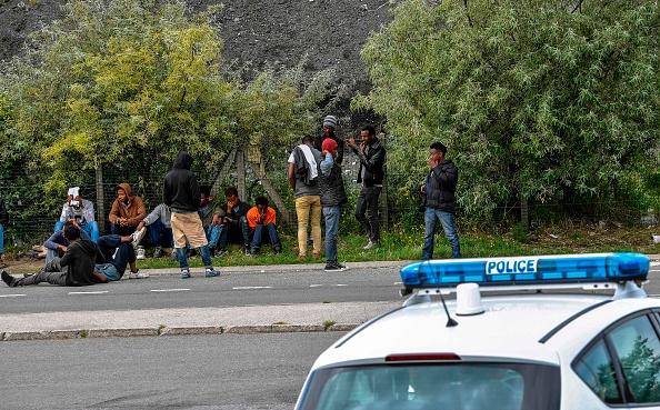 法國加萊港口附近聚集的企圖偷渡者,一輛警車正在監視他們。( PHILIPPE HUGUEN/AFP/Getty Images)
