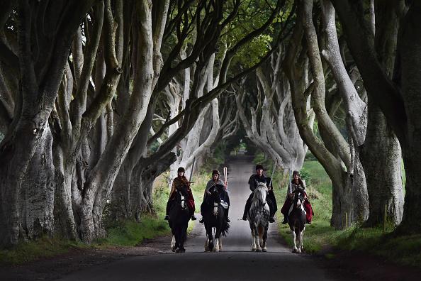 图为四名演员身穿《权力游戏》的戏服骑马从黑暗树篱经过,他们手中拿的是2018年澳大利亚主办的英联邦运动会的火炬。( Charles McQuillan/Getty Images)