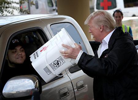 9月2日,川普夫婦訪問德州東南部受哈維颶風襲擊嚴重的地區。圖為川普準備將救災物品裝到一位受災居民的車上。 (Win McNamee/Getty Images)