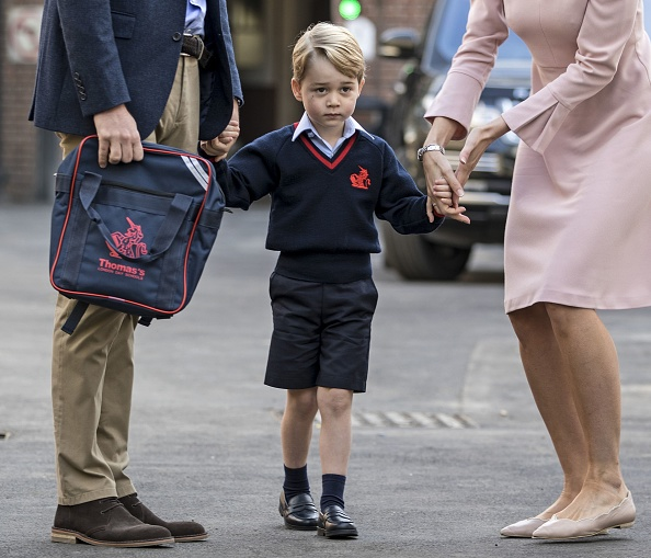 Britain's Prince George (C) accompanied by Britain's Prince William (L), Duke of Cambridge arrives for his first day of school at Thomas's school in Battersea where he is met by Helen Haslem (R) head of the lower school. / AFP PHOTO / POOL / RICHARD POHLE (Photo credit should read RICHARD POHLE/AFP/Getty Images)