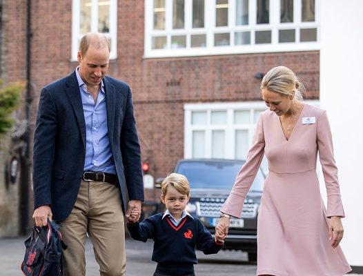 威廉王子替喬治王子拿著書包,從車上下來後一起走人學校入口,在那裡受到學校低年級主管海倫·哈斯勒姆女士的迎接與問候(Helen Haslem)( RICHARD POHLE/AFP/Getty Images)