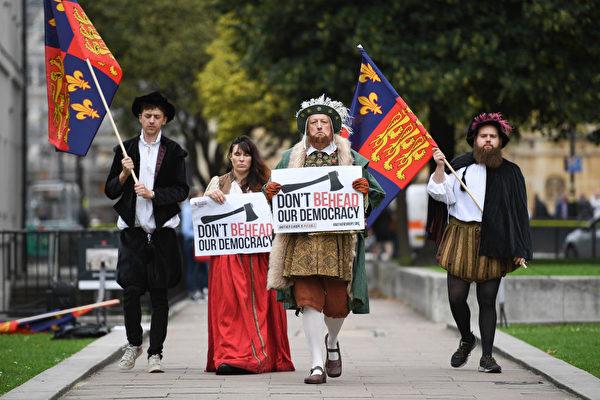 連亨利八世都要跟脫歐扯上關係。 9月7日議會下議院首次舉行「脫歐議案」的辯論。場外,抗議者身穿亨利八世時代的服裝,手裡舉著「不要把我們的民主砍頭」的標語。「脫歐議案」的一些內容受到批評,因為政府會擁有一些新的權力,有可能會對民主構成威脅,因此被一些人稱為「亨利八世條款」。(Leon Neal/Getty Images)