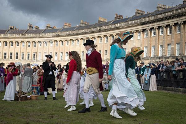這是什麼舞會?伊麗莎白•班尼特和達西先生第一次見面的舞會嗎? 9月9日,英格蘭城市巴斯迎來了一年一度的簡•奧斯汀節(Jane Austen Festival)。圖為身穿奧斯汀時代服裝的人們在巴斯最有名的建築皇家新月樓(Royal Crescent)門前的草坪上跳舞,然後遊行穿過市中心。 奧斯汀曾經在巴斯居住了六年。今年是她去世200周年。奧斯汀節將持續十天。(Matt Cardy/Getty Images)