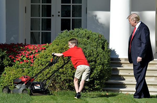 2017年9月15日上午,美国总统川普在白宫的玫瑰花园观看11岁小男孩弗兰克推草坪。(Win McNamee/Getty Images)