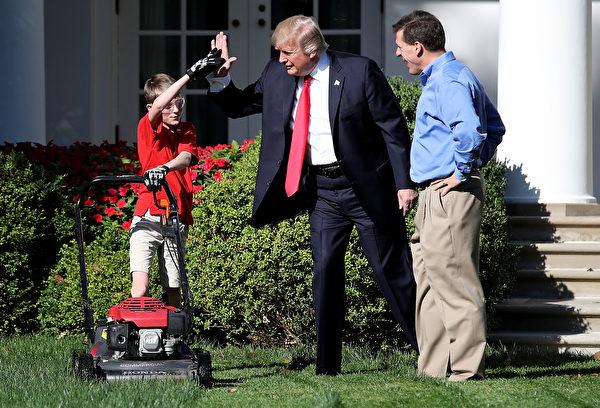 2017年9月15日上午,美国总统川普带着小弗兰克父子俩在白宫的玫瑰花园推草坪时,和他击掌相庆。(Win McNamee/Getty Images)