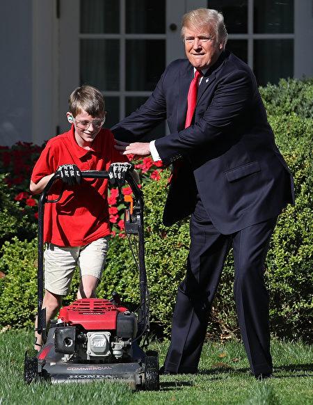 2017年9月15日上午,美国总统川普在白宫的玫瑰花园和11岁的维吉尼亚州男孩弗兰克一起修剪草坪。(Win McNamee/Getty Images)
