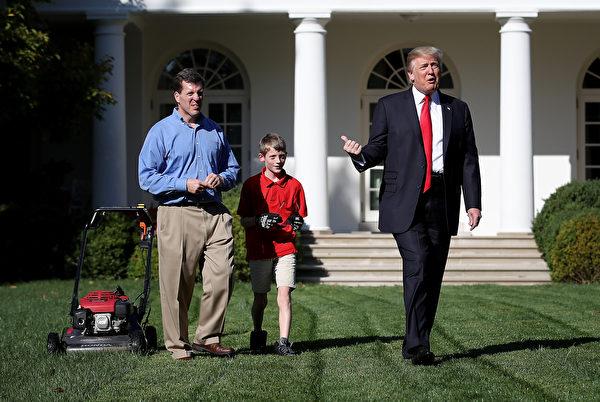 2017年9月15日上午,美国总统川普带着小弗兰克父子俩在白宫的玫瑰花园推草坪时,拍拍他的后背。(Win McNamee/Getty Images)