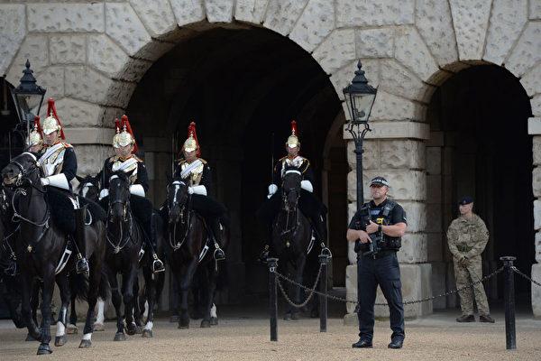 恐怖襲擊過後,9月16日,英國皇家騎兵隊離開皇家騎兵閱兵場,旁邊是全副武裝的倫敦警察。(CHRIS J RATCLIFFE/AFP/Getty Images)