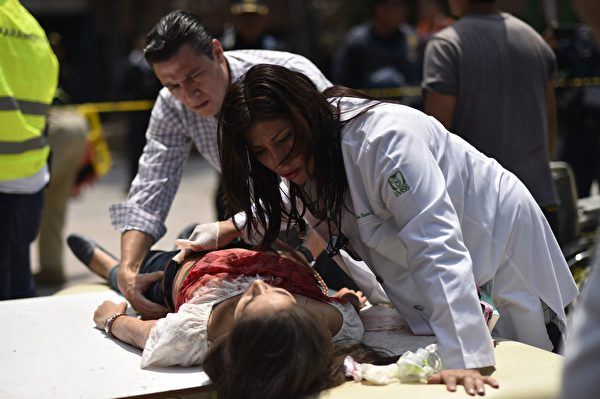 9月19日墨西哥城發生7.1級強震,造成至少上百人遇難。圖為當地救援者和志願者正在搶救傷者。(PEDRO PARDO/AFP/Getty Images)