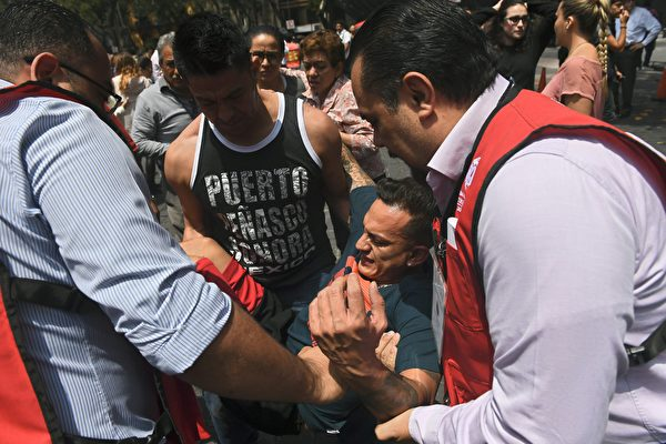 An injured person gets help after a powerful quake in Mexico City on September 19, 2017. A powerful earthquake shook Mexico City on Tuesday, causing panic among the megalopolis' 20 million inhabitants on the 32nd anniversary of a devastating 1985 quake. The US Geological Survey put the quake's magnitude at 7.1 while Mexico's Seismological Institute said it measured 6.8 on its scale. The institute said the quake's epicenter was seven kilometers west of Chiautla de Tapia, in the neighboring state of Puebla. / AFP PHOTO / Pedro Pardo (Photo credit should read PEDRO PARDO/AFP/Getty Images)