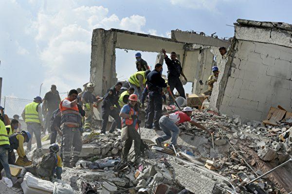 9月19日墨西哥城發生9.1級強震,造成至少上百人死亡。圖為救援者和志願者在瓦礫中尋找倖存者。 (ALFREDO ESTRELLA/AFP/Getty Images)
