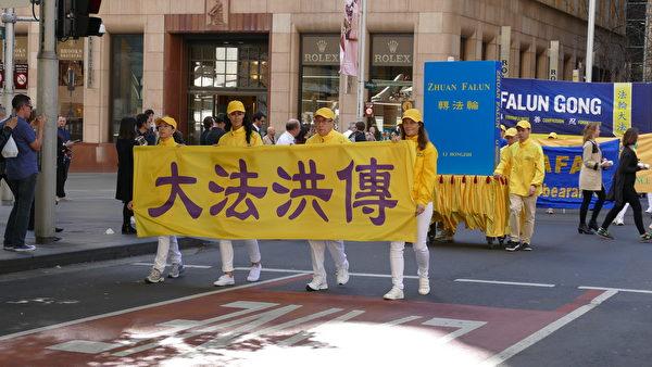 9月8日,澳洲法輪功學員的遊行隊伍穿過悉尼市商務中心,附近上班族駐足觀看。(安平雅/大紀元)