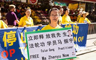 紐約法輪功學員張玉華21日在聯合國門前舉牌呼籲營救他兩天前剛被抓走的丈夫、南京法輪功學員馬振宇。(戴兵/大紀元)