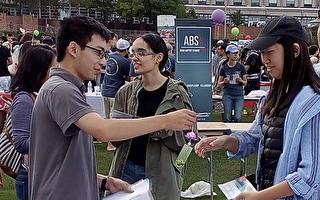 美国波士顿大学学生在社团博览会上了解法轮功真相。(明慧网)