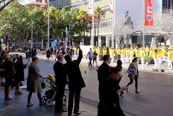 9月8日上午,澳洲法輪功的大煉功為著名旅遊景點的環形碼頭增添了一道特殊的風景線。人們駐足觀看,紛紛用手機照相。(攝影:何蔚/大紀元)