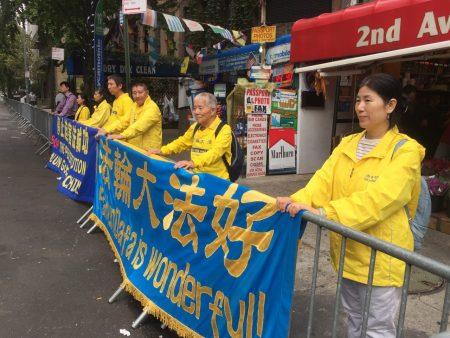 法輪大法學員顧吉米(右三)9月18日在曼哈頓第50街與第二大道交口處舉橫幅講真相。 (施萍/大紀元)