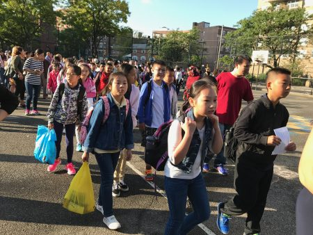 开学第一天,法拉盛第20小学的华裔学生背着书包、拿着新买的文具,排队进入校门。