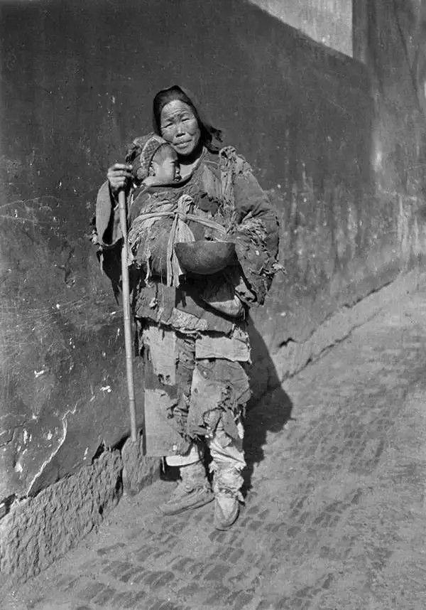 北京街头的一位老年乞丐,她怀中还抱着一个孩子,摄于1917-1919之间。(甘博/公有领域)