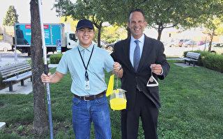加州食品農業局專員David Pegos(右)拿著捕蠅籠表示,要將果實蠅一網打盡。(李文淨/大紀元)