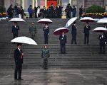 中共十九大于10月18日在北京的秋风凄雨中开幕。图为保安人员撑著雨等待代表到来。(AFP PHOTO / Greg Baker)