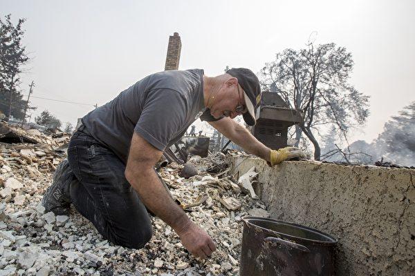 北加州发生有史以来最惨重的火灾,至少3500栋建筑物烧毁,近3000人失联。图为2017年10月10日,加州圣塔罗莎,一位民众在他被烧毁的房子中寻找留存的东西。(David McNew/Getty Images)