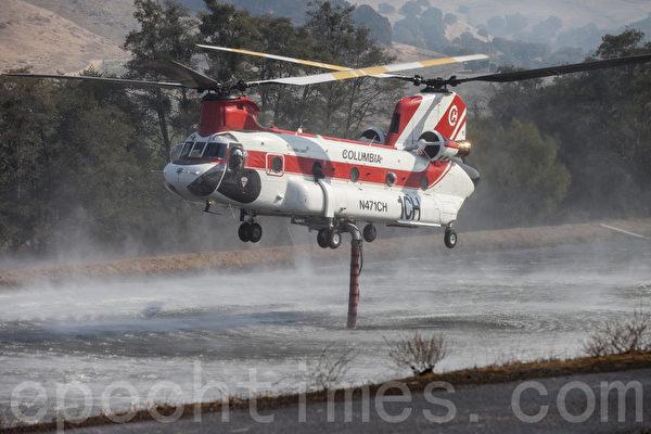 消防直升机在葡萄园的水塘里吸水后飞到火场灭火