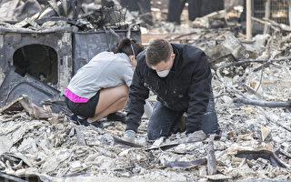 在美國空軍服役的Joseph Brown和太太,回到燒成廢墟的家園找尋物品。(曹景哲/大紀元)