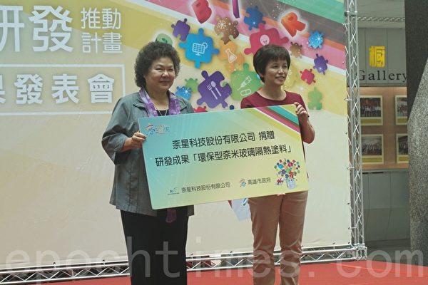 SBIR廠商將研發環保型奈米玻璃隔熱塗料技術獻給市府,市長陳菊(左)特地予以鼓勵。(李怡欣/大紀元)