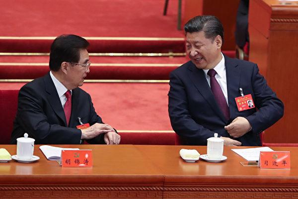 中共「十九大」18日起在北京召開。圖為習近平(右)宣讀完「十九大」報告後,回到主席台與胡錦濤(左)握手並談笑風聲。 (Lintao Zhang/Getty Images)