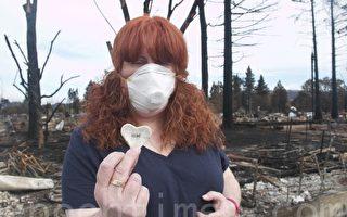 """居民Susan Gray在被大火烧毁的家园废墟中,找到了一个写有""""希望""""(hope)字样的心形饰品,期待重建家园。(李文净/大纪元)"""